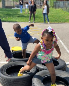 two preschool age children boy and girl stepping through tires and obstacle course
