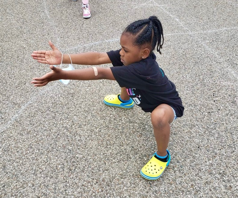 young girl doing ballet move outside in parking lot