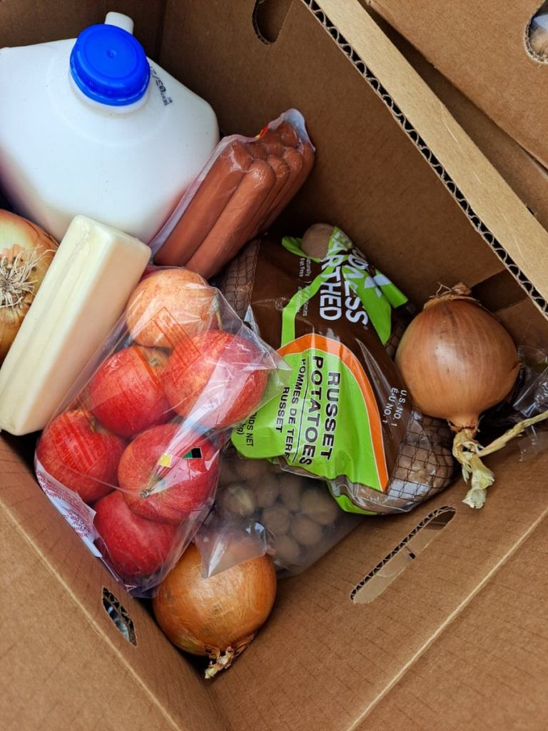 box filled with milk, cheese, fruits and vegetables