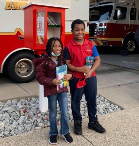 boy and girl holding books, in front of little library box at fire station