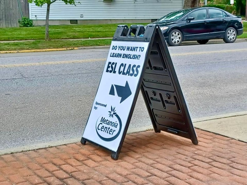 sign on sidewalk advertising English as a second language class