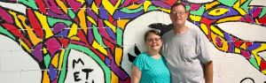 couple standing in front of wall painted with colorful mural