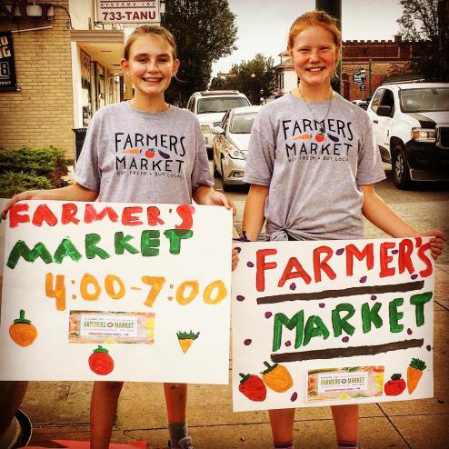 two young girls holding signs for farmers market