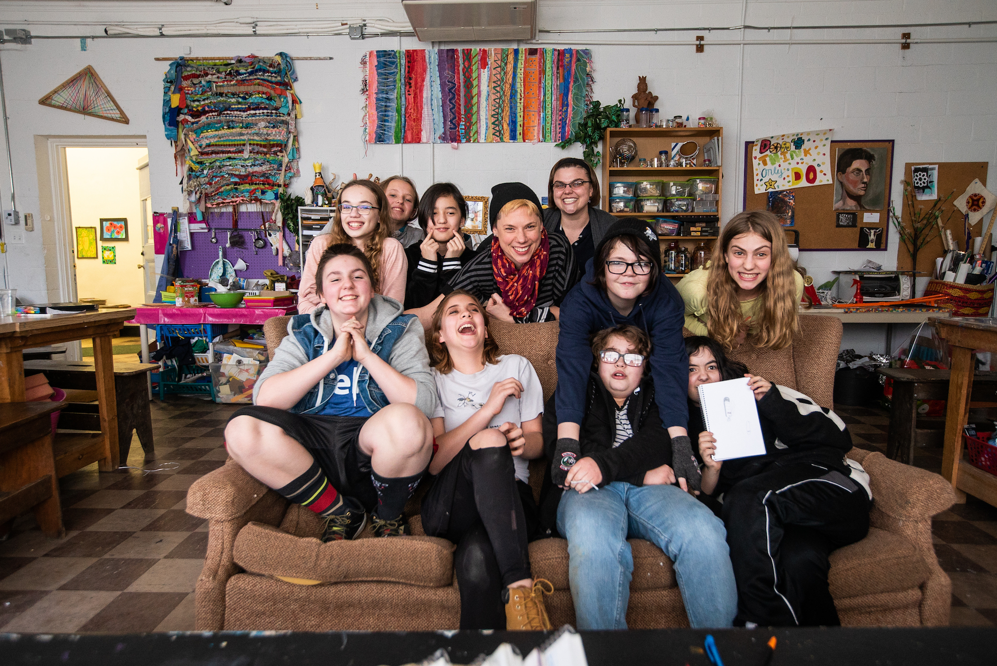 An image of a group of students smiling and laughing sitting on a couch in an art studio.