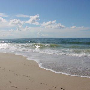 Das kommende Wasser, die Flut an einem Sandstrand mit blauem Himmel
