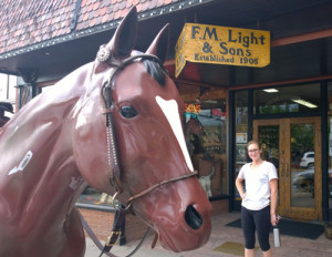 Model horse and young woman in front of F.M. Light & Sons