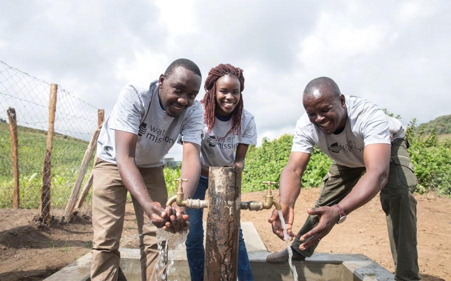 Water Mission Kenya staff rejoice over their hard work to see safe water flowing in Enariboo, Kenya.