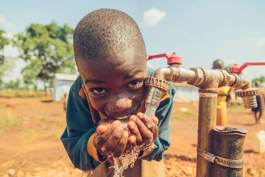 Young boy drinks safe water from a tap in Nyarugusu Refugee Camp, Tanzania.