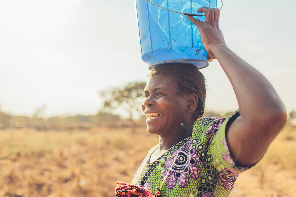A woman in Malawi smiles because of safe water.