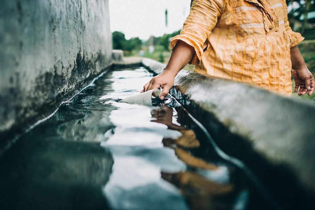 A woman in Indonesia collects dirty water to wash dishes.