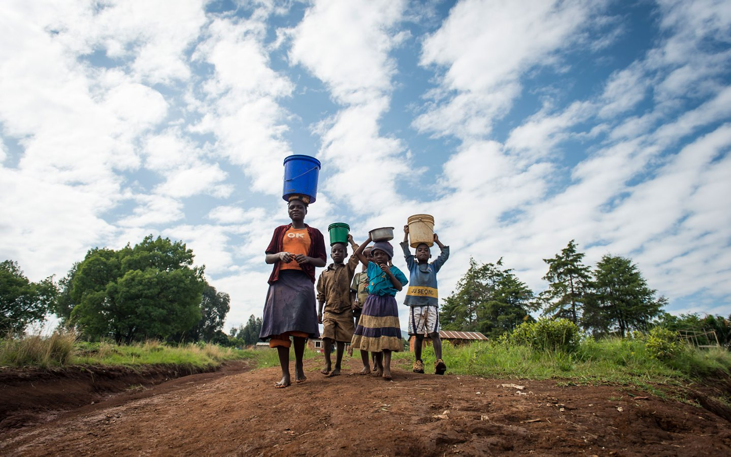 A family in Tanzania walk with buckets of water on their heads.