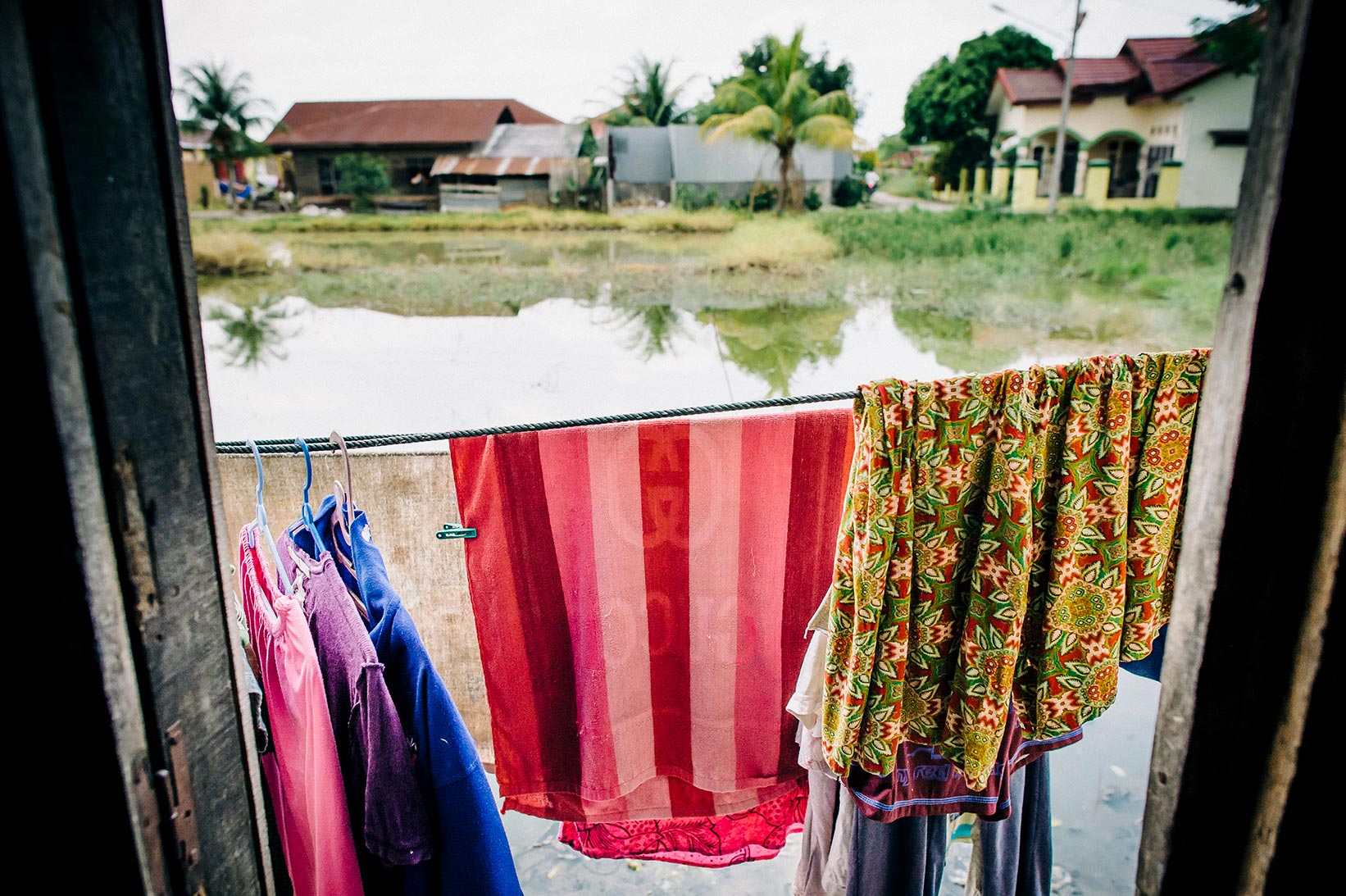 Clothes hang up to dry outside a woman's home in Indonesia.