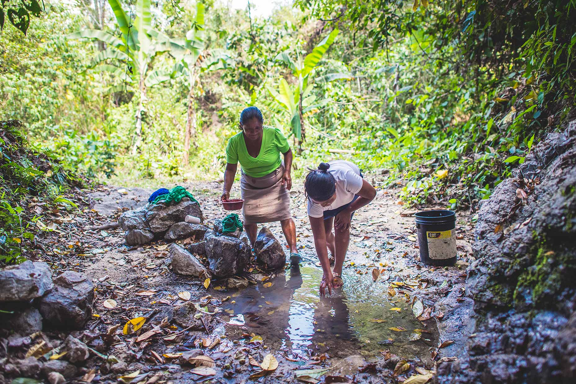 Honduras women wash clothes in the small water source near their house.