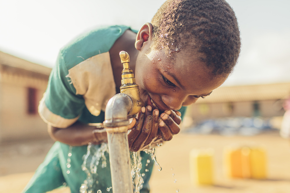 Dina drinks safe water from a Water Mission tap stand at her school.