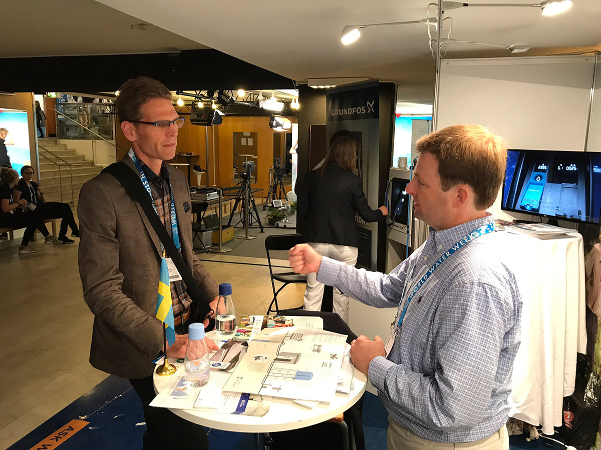 George Greene, PE speaks with an interested SIWI attendant at World Water Week.