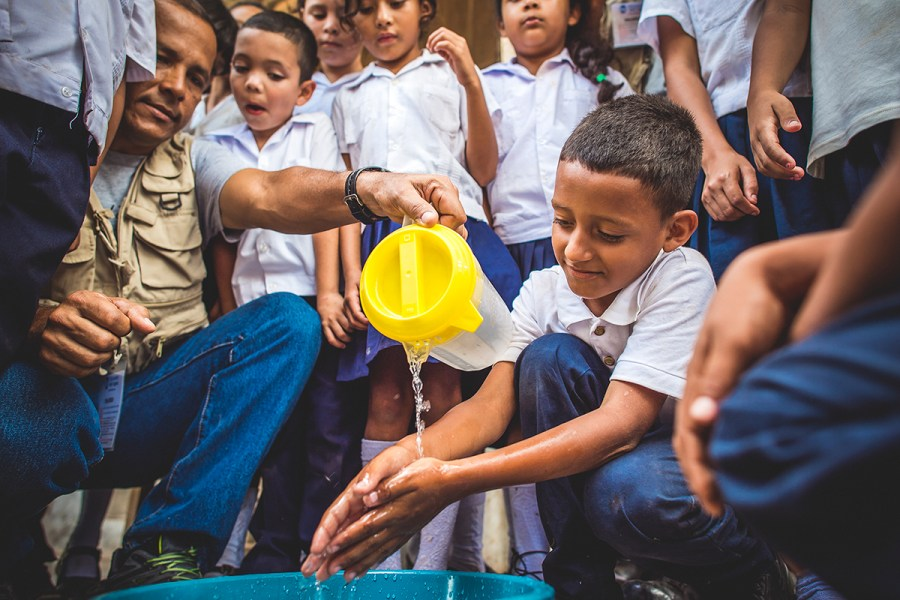 A young boy in Honduras washes his hands with safe water.