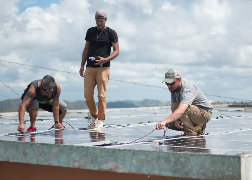Tim Darms (Project Engineer) installs solar panels to power safe water systems.