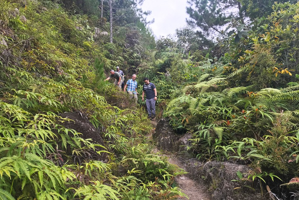 Kevin and a team of leaders hike a steep hill in North Sumatra, Indonesia.