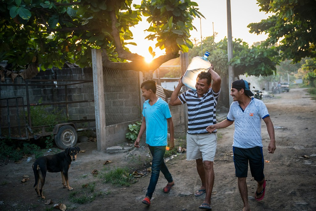 Raul and his sons carry safe water to the restaurant.