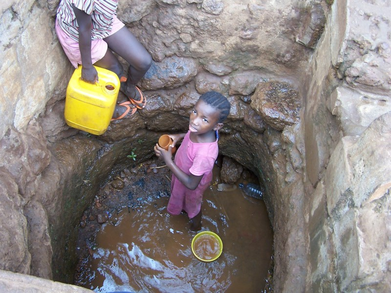 girls collects dirty water from a well in Africa.