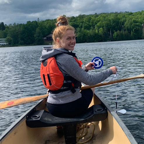 Une femme mesure la profondeur de l'eau à l'aide d'un disque de Secchi et d'une bobine sur le côté d'un canoë. Elle est en eau profonde.