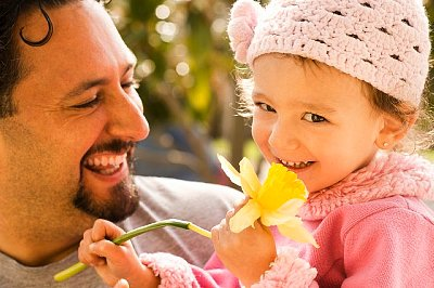 Father smiling at daughter with flower