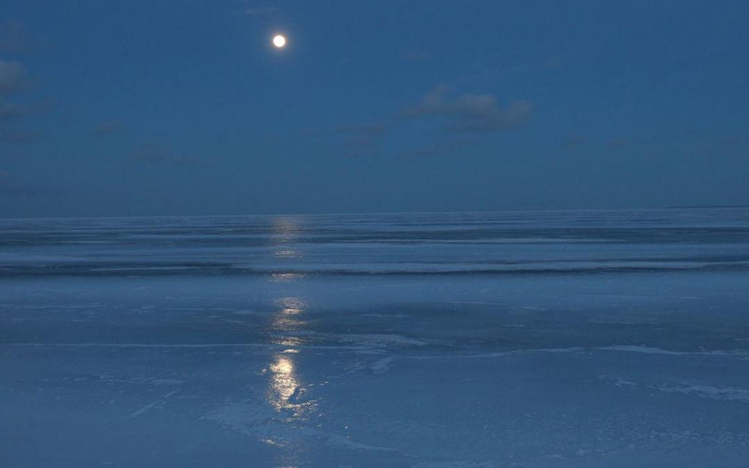 This is a photo of Lake Superior. The moon is full and the lake is frozen, casting a bluish light.