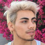 This is a head shot of the writer JJ Pena. JJ has bleach blonde, wavy hair that is close-cropped on the sides. They have dark brown eyebrows and a goatee and mustache. They are looking away from the camera and are surrounded by bright pink flowers.