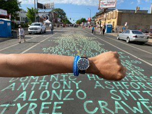 This is a photo by photographer Alex Soth. It features a person's extended arm hovering over a city street with names of victims of police violence written on the street. The arm is wearing a large blue watch on their wrist.