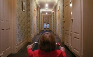 This is an image from Stanley Kubrick's film The Shining. In this photo, a young boy with brown hair and a red shirt is riding a bicycle through a wallpapered hallway when he sees two twin girls wearing identical blue dresses standing side-by-side at the end of the hallway.