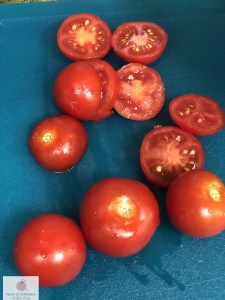 Sliced tomatoes on blue cutting board