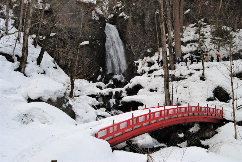 越過紅色小橋,眺望不動瀑布的雪景