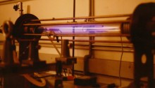 Laboratory scale Z-pinch showing glow from an expanded hydrogen plasma. Pinch and ionisation current flows through the gas and returns via the bars surrounding the plasma vessel.