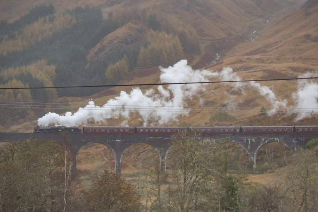 The Jacobite Railway crosses the Glenfinnan Viaduct, the highligh of any Scotland road trip