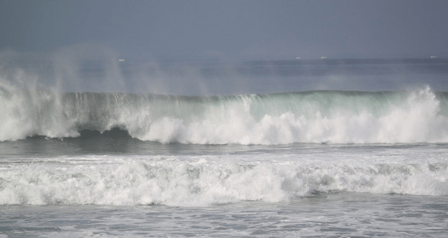 a sea green wave breaks into foamy white wash at a beach in southern california