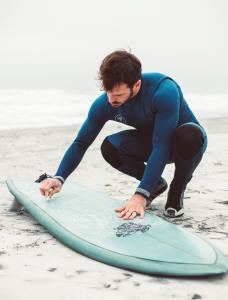 Man in a wetsuit waxing his surfboard.
