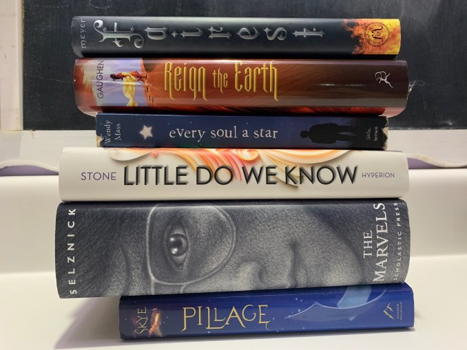 "A stack of 6 books whose titles read, from top to bottom, ""Fairest. Reign the Earth. Every Soul a Star. Little Do We Know. The Marvels. Pillage."""