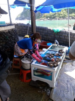 Haenyeo woman working at their shop with freshly caught seafood in tanks
