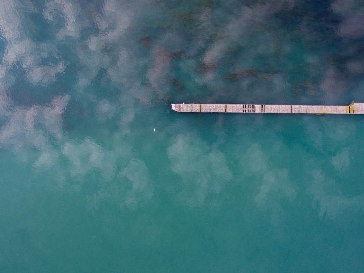 aerial shot of a lake in Michigan and a long wooden jetty with planks missing. According to the photographer taken at Belle Isle, Detroit, Michigan, United States