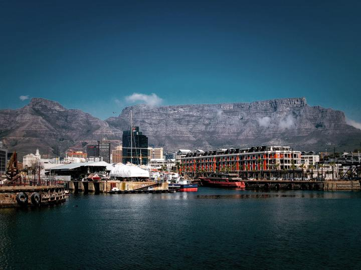 In the background is a large flat topped mountain. In the foreground is a city, the viewer is in the ocean looking inward at the boats and port and the city between the ocean and mountains. Taken according to the photographer at V&A Waterfront, Dock Road, Cape Town, South Africa