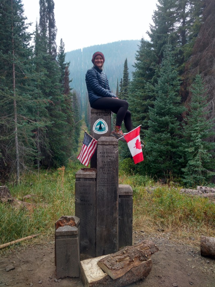 Photo of Canadian and American unmmaned boarder in the middle of the woods at the end of the PCT with Kristin. The marker is made of different levels of stone with flags sticking out of it and a trail marker. Atop the highest one sits Kristin.