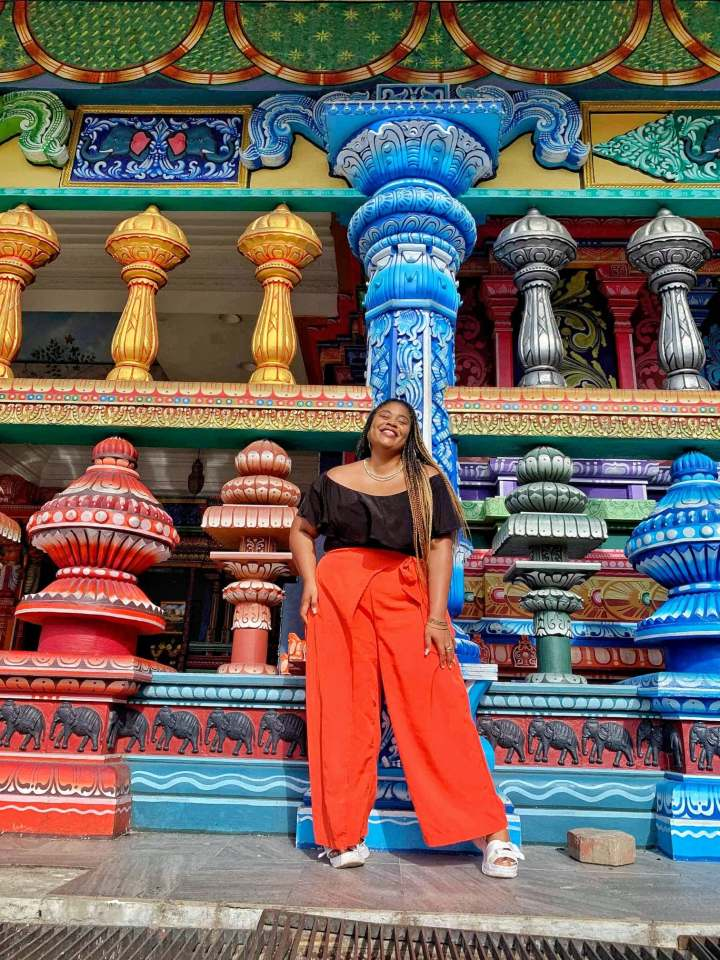Nathalie at the Batu Caves in Malaysia, in front of colorful pillars and temple