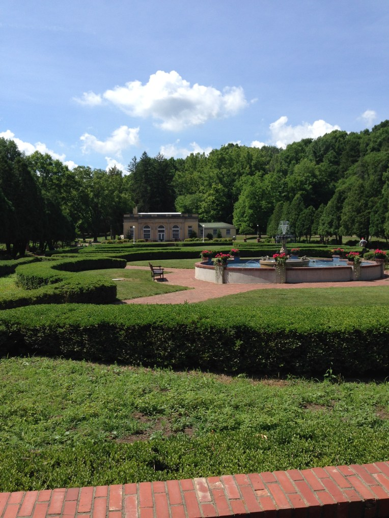 The formal gardens with a view of the old bowling alley in the back. This building is closed to the public as it is frequently flooded by the nearby stream.