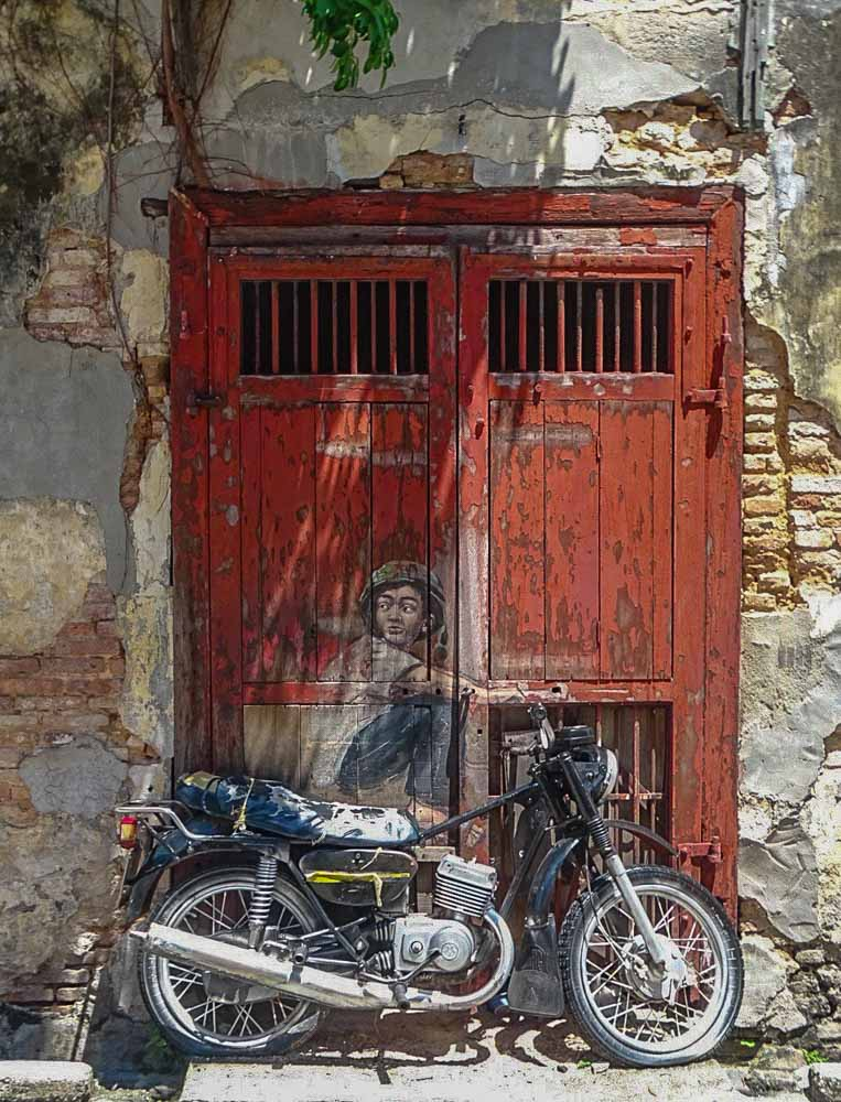 Malaysia Penang motorbike mural. Boy street art with motorcycle.