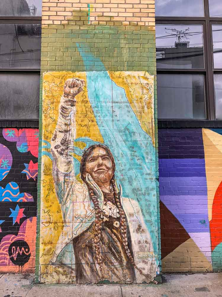 Brooklyn mural of Native American with fist raised by Lanopi