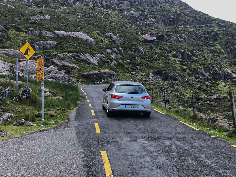 Self Drive in Ireland on Conor Pass. Single car driving on a narrow road.