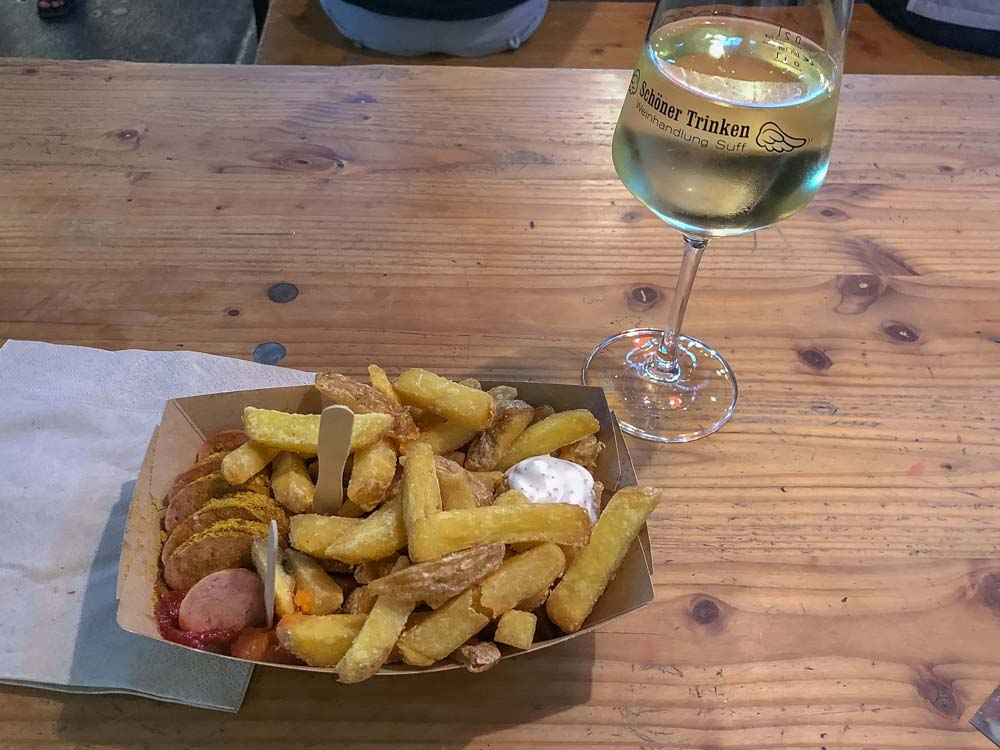 Currywurst in Berlin Germany- platter of sausage with french fries and white wine