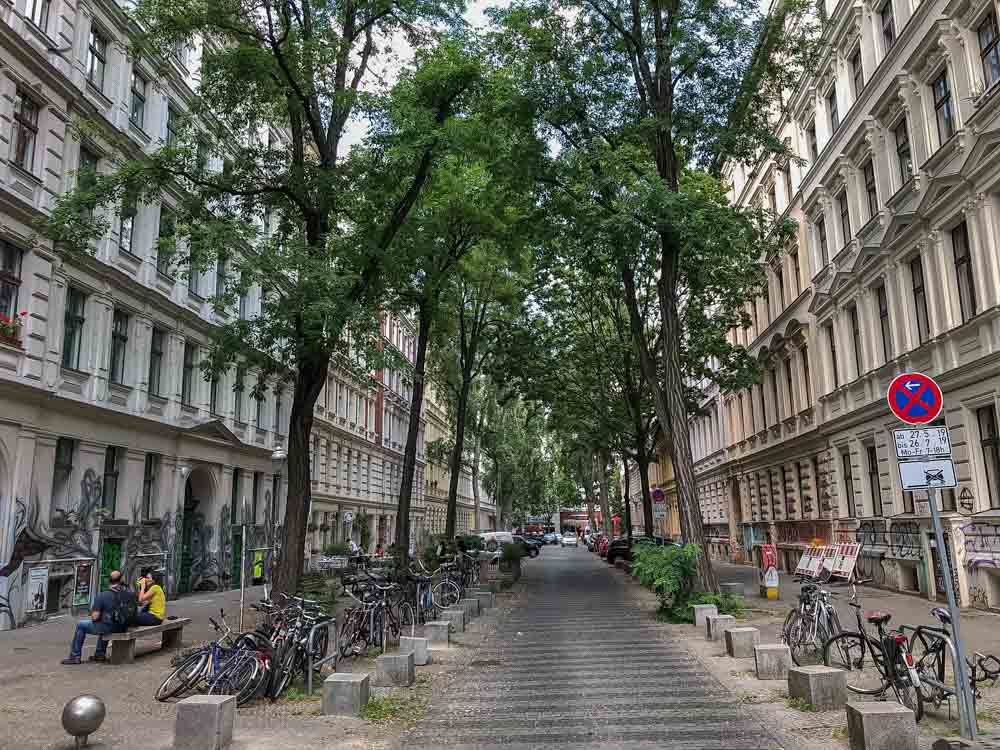 Kreuzberg Berlin street with trees, cars and a road