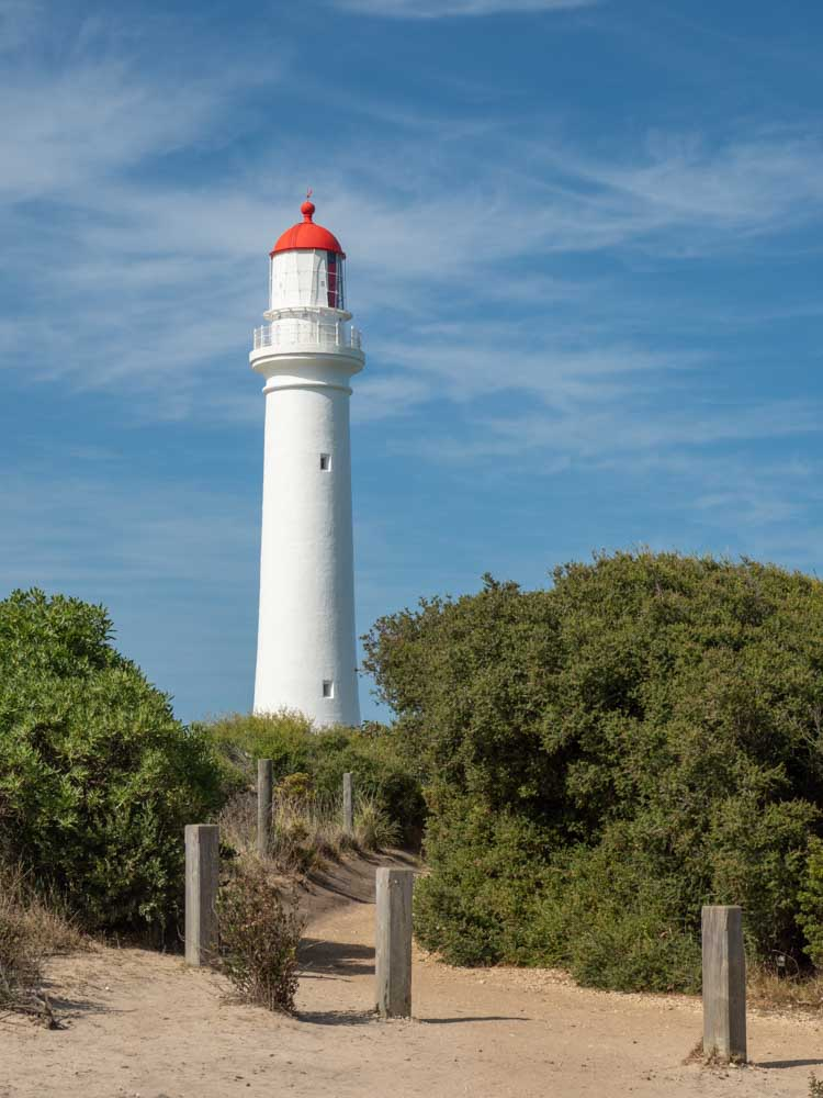 Split Point Lighthouse on the Great Ocean Road. White lighthouse with red top and trees