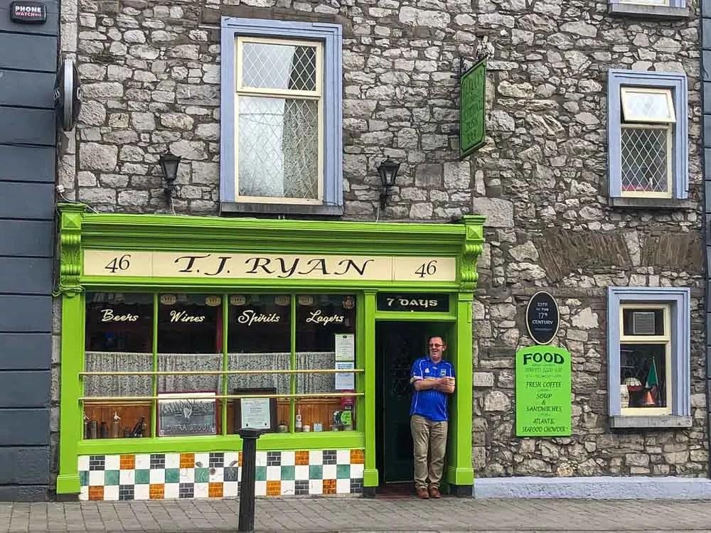 TJ Ryan's Pub in Cashel Ireland. Man in front of green doorway with rock wall